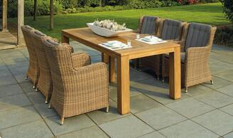 A concrete patio sits next to a mowed lawn. A posh outdoor table sits on the patio with set of six chairs.