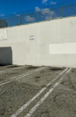 A parking lot bakes in the sun and cracks have risen up as the concrete breaks under pressure.
